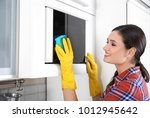 young woman cleaning microwave... | Shutterstock . vector #1012945642