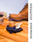 Small photo of Footwear Concepts.Closeup of Premium Tan Brogue Boots Along with Cleaning Accessories and Cleaning Cloth.Vertical Image