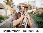 Stock photo happpy young bearded farmer holding two little kitten in hands outdoor in village with abstract 1013001232