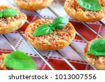 Small photo of Close up of Mini pizas baked with tomato, oregano and basil on red and white checkered table coth.
