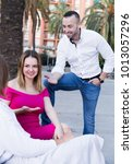 Small photo of Young male is acquaintance with girls who are sitting on bench in the park.