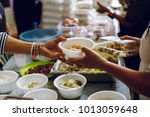 feeding the poor to hands of a... | Shutterstock . vector #1013059648