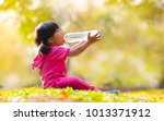 little girl drinking water over ... | Shutterstock . vector #1013371912