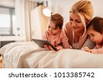 mother and two baby girls... | Shutterstock . vector #1013385742