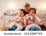 mother holding two baby girls | Shutterstock . vector #1013385745
