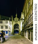 Small photo of Braga, Portugal. August 14, 2017: Night view of the arch called the new door with people walking, very illuminated and with shops already closed