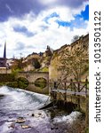Small photo of Blue Skies and the Alzette River with Waterfall surrounded by Spring Blossoms at the Bock Casement Ruins in Luxembourg City, Luxembourg, Vertical Orientation