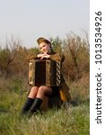 Small photo of Pretty Soviet female soldier in uniform of World War II sits with an accordion on a suitcase