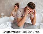 sad man sitting on bed with his ... | Shutterstock . vector #1013548756
