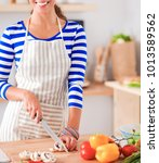 young woman cutting vegetables...   Shutterstock . vector #1013589562