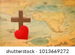 Small photo of For God so loved the world - A Cross on a rustic world map