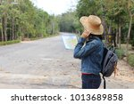 a backpacking woman holds map... | Shutterstock . vector #1013689858