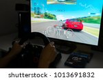 Small photo of Melbourne, Australia - Jan 30, 2018: A man playing Gran Turismo Sport on PlayStation 4 Pro with steering wheel at home. GT Sport is a popular racing game developed by Polyphony Digital.