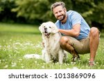 man plays with his dog as... | Shutterstock . vector #1013869096