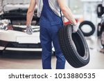 mechanic holding a tire tire at ... | Shutterstock . vector #1013880535