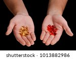 Small photo of Softgel pills on male hands. Yellow and red capsules for best absorption. Studio shot, isolated on black.