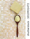 Small photo of Shea butter in wooden spoon, homemade olive oil soap on yellow tile background with copyspace
