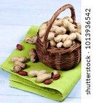 peanuts with nutshell in wicker ... | Shutterstock . vector #1013936542