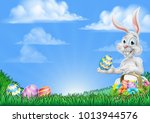 Stock vector an easter bunny rabbit with basket of easter eggs on an egg hunt pointing with space for a message 1013944576