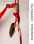 Small photo of Beautiful aerialist girl doing acrobatic and flexible tricks on red aerial silks (tissues) on white background