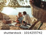 a young couple having a picnic... | Shutterstock . vector #1014255742