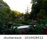 Small photo of Flowers abound in this garden view near a pond with a pirate ship replica in the background, Tivoli Gardens in Copenhagen Denmark
