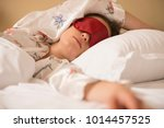 tired woman sleeping in bed... | Shutterstock . vector #1014457525