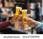 beer glasses raised in a toast. ... | Shutterstock . vector #1014734995