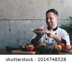 young chef cooking in kitchen. | Shutterstock . vector #1014748528