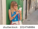 cute woman holding cellphone in ... | Shutterstock . vector #1014768886