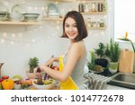 young asian woman making salad... | Shutterstock . vector #1014772678