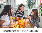 mother and daughters sitting at ... | Shutterstock . vector #1014838282