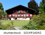 Small photo of Grindelwald, Switzerland - September 21, 2017: Traditional Alpine house. The facade with many windows is decorated with flowers and additionally it is beautified by red painted shutters.