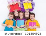 Happy kids laying on the floor holding books - the colorful world of reading - stock photo