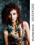 Small photo of Beautiful bright woman with curly foxy hair wears a beads and earrings in boho style. Ethnic style in accessories.