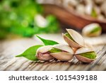 pistachios nuts on wooden table.... | Shutterstock . vector #1015439188