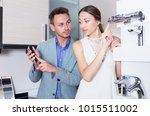 positive young couple choosing... | Shutterstock . vector #1015511002