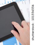 Modern business analyst working with digital tablet computer, sheet and graphs. Vertical composition, top view. - stock photo