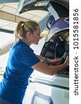Small photo of Female Aero Engineer Working On Helicopter In Hangar