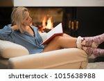 blonde women by a fire place... | Shutterstock . vector #1015638988
