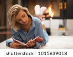 blonde women by a fire place... | Shutterstock . vector #1015639018