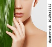 Small photo of Skincare, Wellness, Spa. Clean soft Skin, healthy Fresh look. The concept of a healthy skin. Portrait of a beautiful girl against a background of tropical leaves. Spa concept. Natural beauty