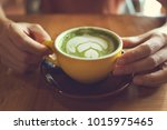 hand holding a cup of hot green ... | Shutterstock . vector #1015975465