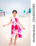 little girl on the beach in... | Shutterstock . vector #1016043382