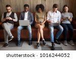 Small photo of Multicultural young people using laptops and smartphones sitting in row, diverse african and caucasian millennials entertaining online obsessed with modern devices waiting in queue, gadget addiction