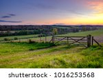 sunset over field gate in the... | Shutterstock . vector #1016253568