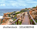 Small photo of Wooden bridge seen from the Oyster Catcher Trail near Mosselbay on the Garden Route in South Africa with rock formations and waves