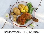 Leg of chicken served with potatoes in jackets - stock photo