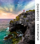 Young female traveller exploring beautiful cliffside coast and pointing out to colourful sunset sky. Gorgeous Canadian landscape. The Grotto, Bruce Peninsula National Park, Tobermory, Ontario, Canada