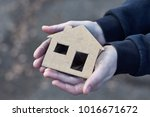 Small photo of young homeless boy holding a cardboard house